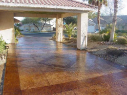Image of a stamped concrete driveway with dark red and light red stain patterns.