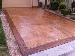 Image of stamped concrete driveway with dark and light red stain details.