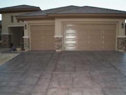 Image of a dark gray random stone concrete overlay driveway.