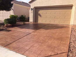 Image of a random-stone overlay concrete driveway with a terracotta-colored stain.