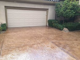 Image of terracotta stained and stamped concrete driveway.
