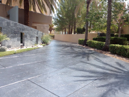 Image of a stamped concrete driveway with a dark granite stain and large block pattern.