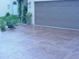 Image of a random-stone stamped concrete driveway with a brown stain.