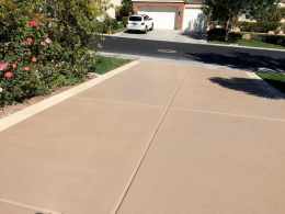 Image of a concrete driveway with a sand-colored spray texture coating.