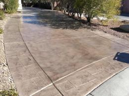 Image of a concrete driveway that's been recolored to a warm gray and resealed.