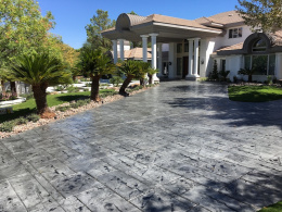Image of terracotta-colored random stone, stained, and sealed concrete driveway.