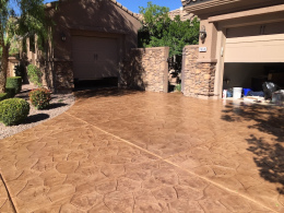 Image of a random-stone stamped concrete driveway with a terracotta stain.