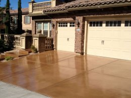 Image of a light brown stain and resealed concrete driveway.