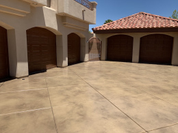 Image of a sand-colored stained concrete driveway.