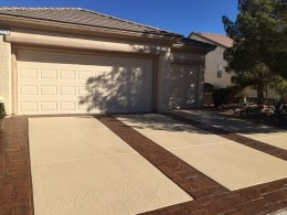 Image of stamped concrete with light sand stain and random stone detail in a dark brown stain on a concrete driveway.