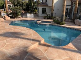 Image of a flagstone overlay concrete poolside with reddish stain.