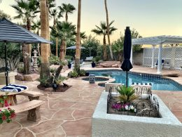 Image of a backyard paradise with a flagstone overlay concrete pool deck and patio.